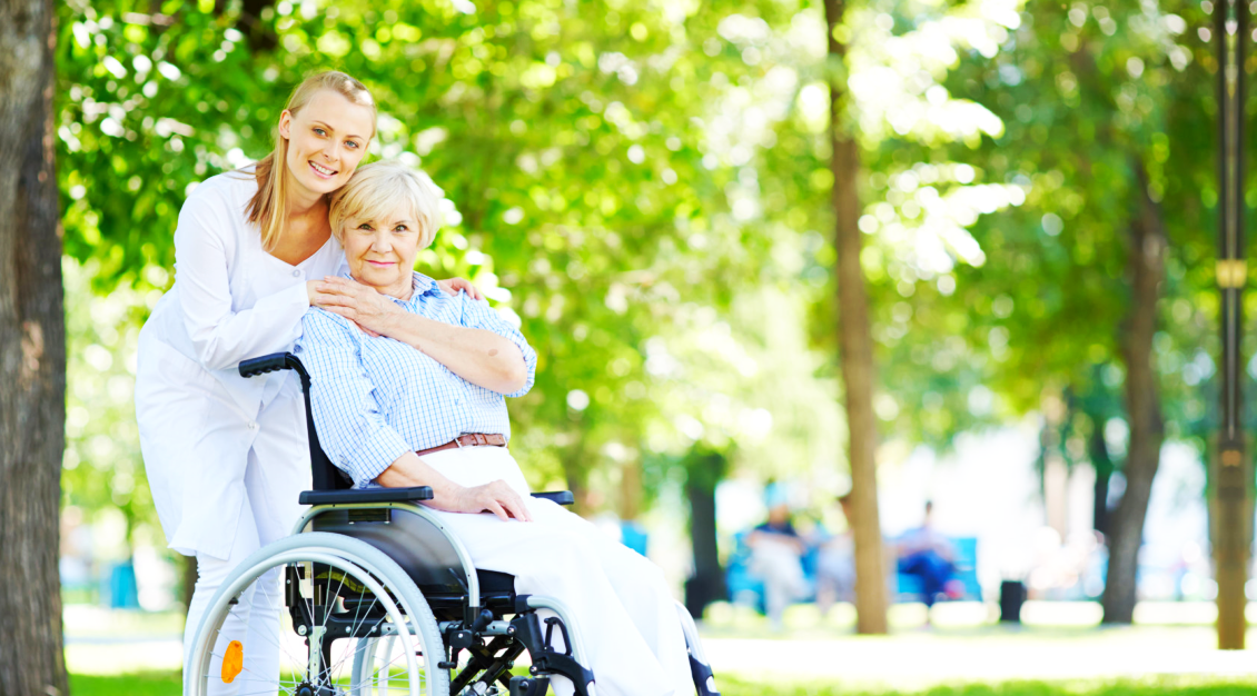 patient in a wheelchair holding the hand of the caregiver